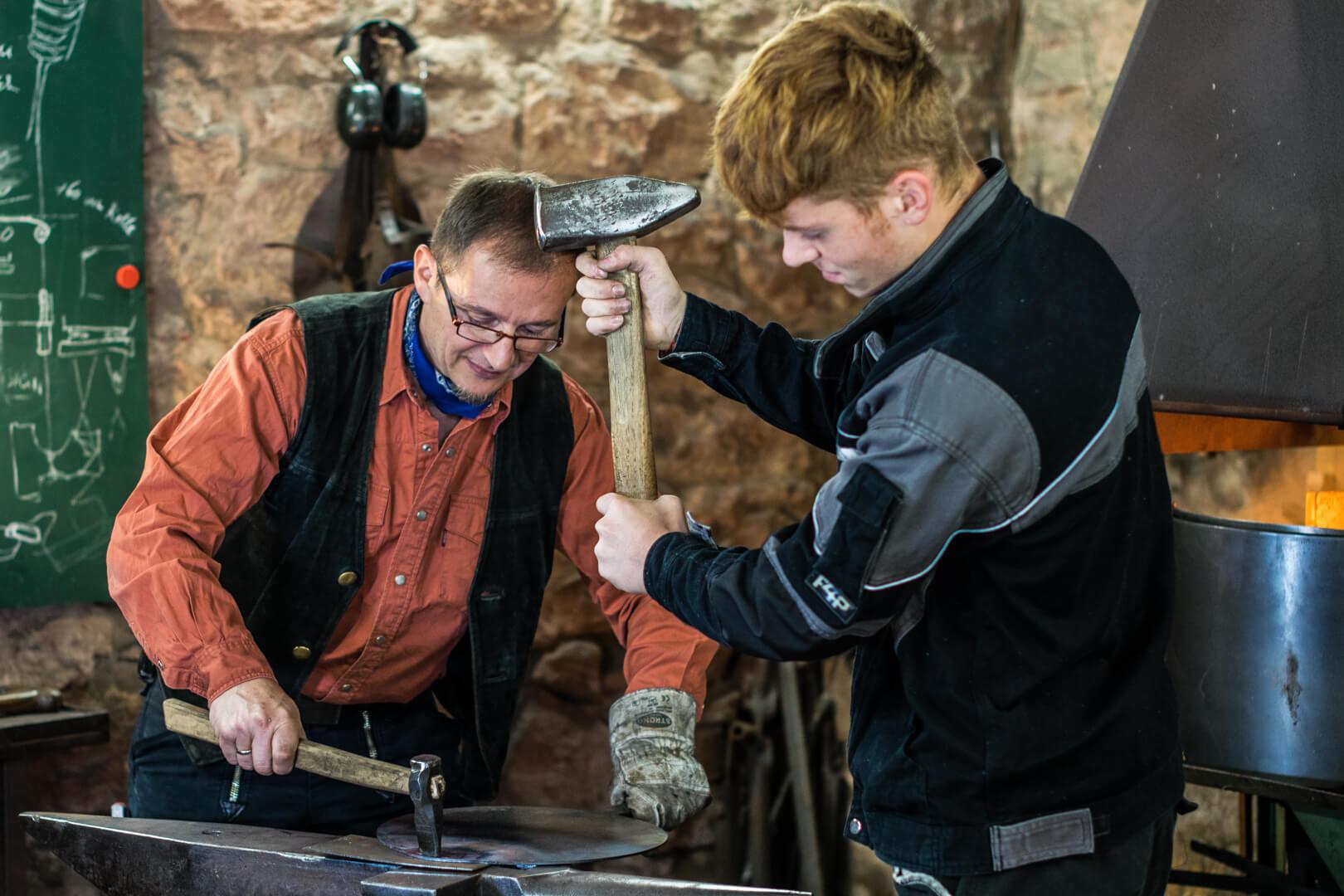 Geselle hämmert und hilft Schmiedemeister beim Bearbeiten des Pfannenrohlings.