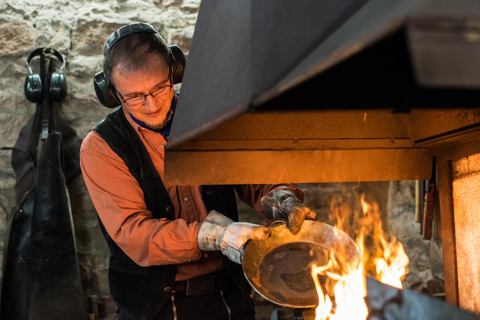 Schmiedemeister erhitzt Pfannenstiel.