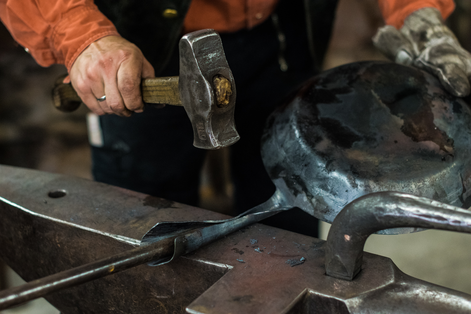 Schmiedemeister rollt den Pfannenstiel um einen Rundstahl ein.